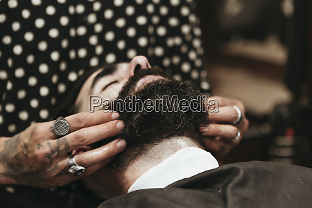 barber styling clients beard at salon