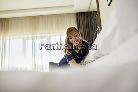 smiling chambermaid making bed while standing