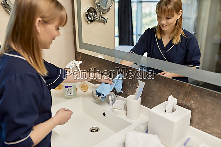 smiling chambermaid wiping faucet of bathroom