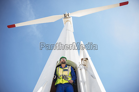 engineer inspecting wind turbine using wrench