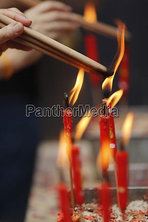 chinese man burning incense and praying