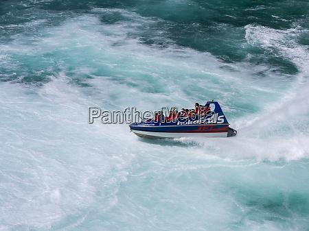 tourists take a speedboat through the