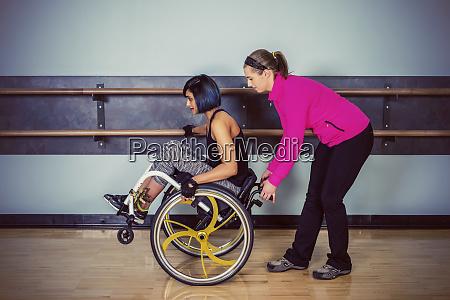 a paraplegic woman popping wheelie in