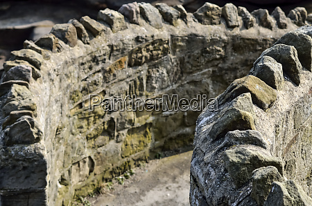 rough crenelated curved stone wall whitley