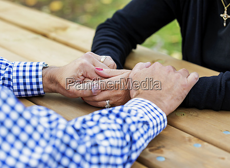 a mature couple praying together at