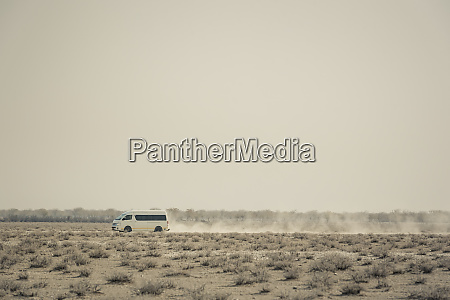 a vehicle driving on a dusty