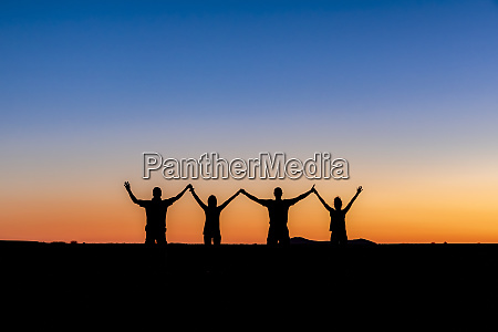 silhouette of four people holding hands