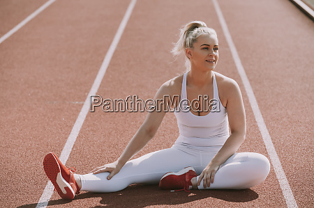 woman sits to stretch her leg