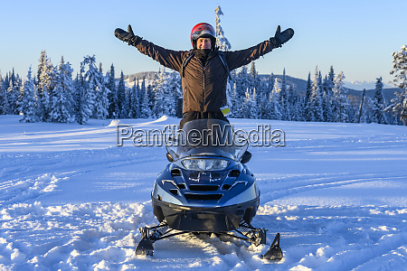 man stands on his snowmobile with