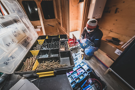 man with toolbox kneeling in a