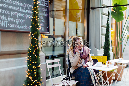 woman using smartphone at cafe firenze