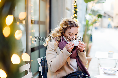 woman having hot drink at cafe