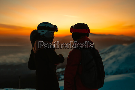 silhouette of two people wearing ski