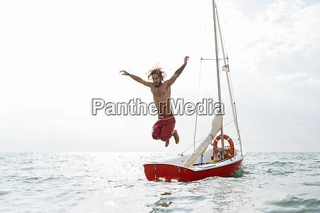 man jumping off sailboat