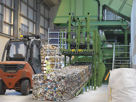 worker inspecting baled waste aluminum cans