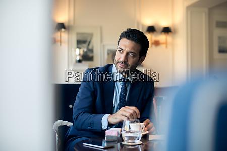 businessman sitting at a table stirring