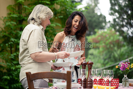 mother and adult daughter setting table