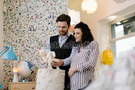 husband and pregnant wife shopping for