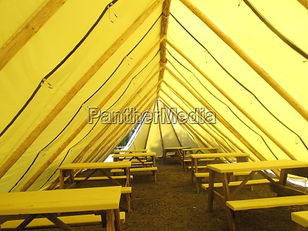 yellow tent with picnic tables and