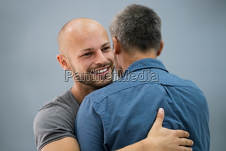 son hugging his happy father