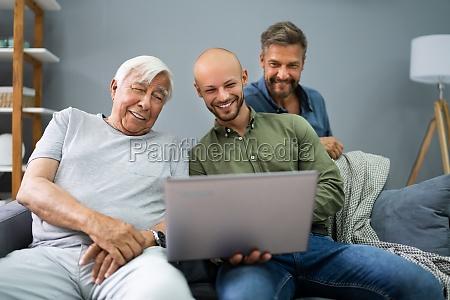 happy three generation men using laptop