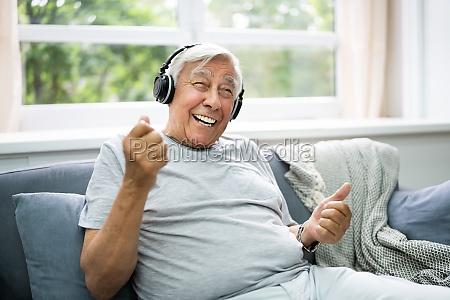 smiling older senior listening music