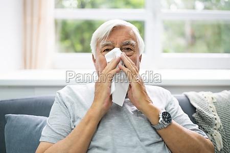 allergic senior man sneezing nose