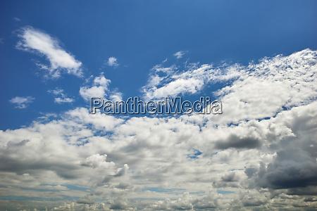 cumulus strewn blue sky in sun