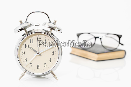silver alarm clock with old books
