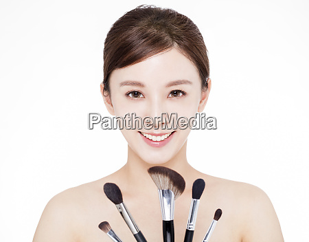 young beauty showing makeup brushes