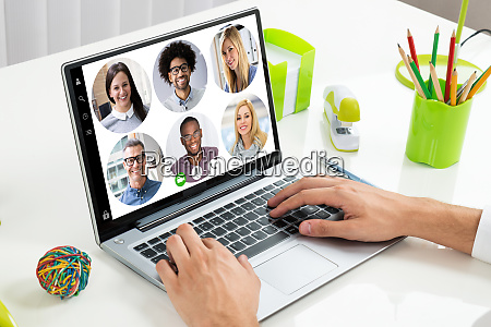 businessperson videoconferencing with colleagues on laptop