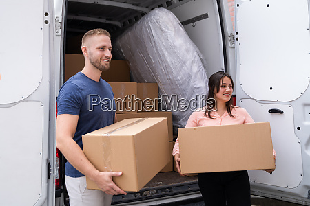 couple moving boxes from van or