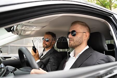 security guard in sunglasses inside car