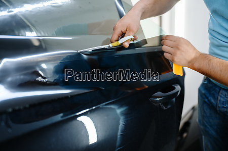 male wrapper holds sunscreen film car