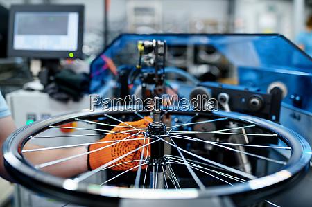 worker checks bicycle rim on backlash