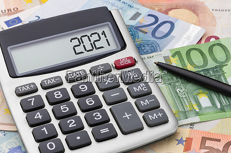 calculator with money and a pen