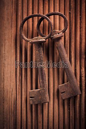 two vintage keys on wooden background