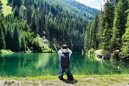 photographer man taking mountain lake photo