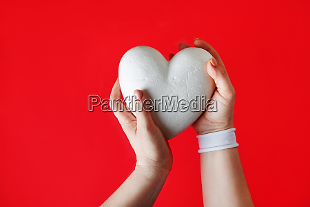 white heart in female hands