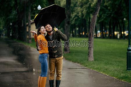 happy love couple enjoys summer rainy