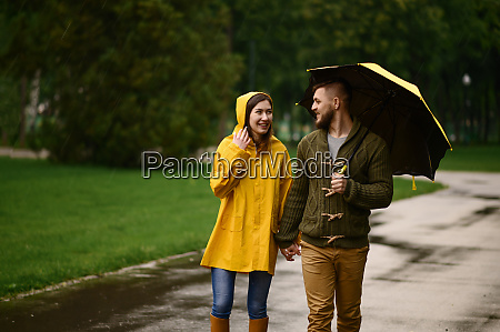 love couple with umbrellas walks in
