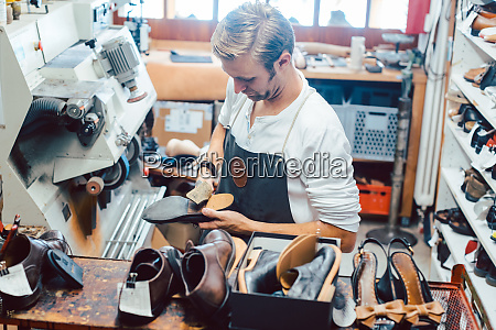 shoemaker with shoes to repair on