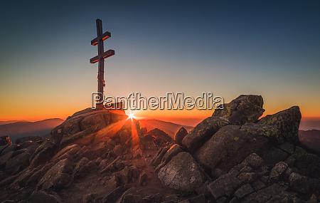 cross on mountain peek at sunset