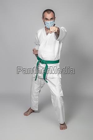 karate practitioner wears a protective mask