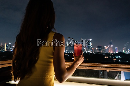 woman having a drink on roof