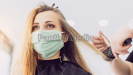 woman visiting the hairdresser wearing face