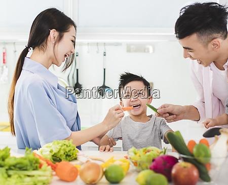 parent feeding boy a piece of