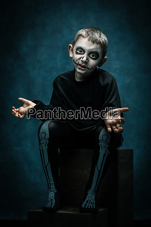 child with ghost makeup face for