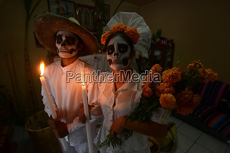 couple depicting a wedding holding candles
