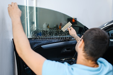 male worker with squeegee installs car
